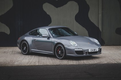 Grey Porsche 911 in front of camouflage aircraft hanger
