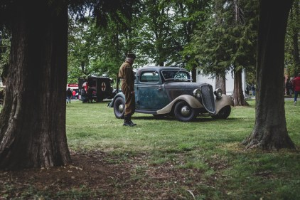 Soldier looking back at vintage Ford motor car