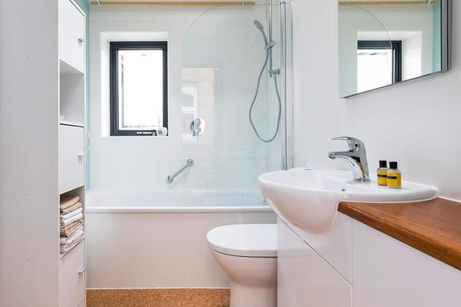 0527 retro bathroom with cork floor and white units near Hampstead Heath