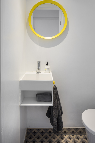 0557 modern cloak room with small white vanity unit and round yellow mirror