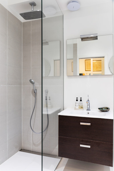 0587 ensuite shower room with wooden vanity unit and brown pattern tiles in marylebone