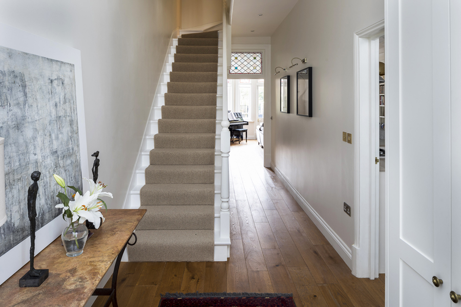 0736 entrance hall and white stairs with beige carpet runner