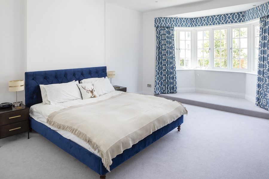 0776 master bedroom with blue bed and curtains and grey carpet in london