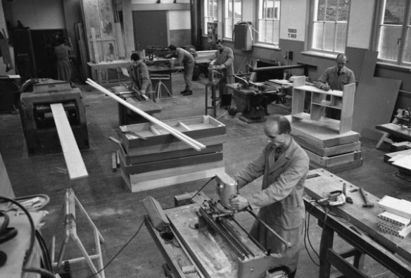 Afd. Machinale houtbewerking in de Ambachtsschool, Bussum.  Kroon staat in het midden (tweede van links), op de voorgrond staat Hans Kuiper, rechtsachter Arie van Bente
