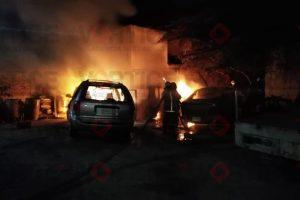 Arden tres vehículos dentro de un taller mecánico
