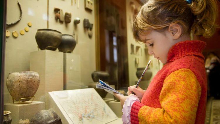 Девочка в музее, записывает информацию в блокнот