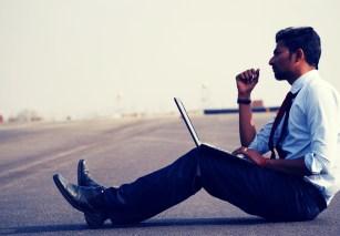 Businessman réfléchissant assis par terre avec son laptop