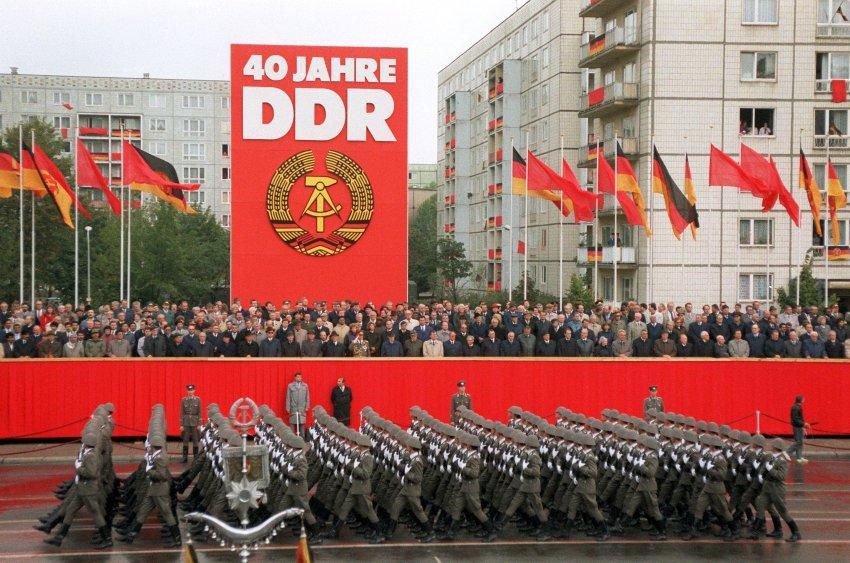 """Das Archivbild vom 07.10.1989 zeigt Soldaten der Nationalen Volksarmee während der Militärparade in Ost-Berlin vor der Tribüne mit der Regierung und den Ehrengästen auf der Karl-Marx-Allee. Die Führung der DDR feiert die Gründung der Deutschen Demokratischen Republik vor 40 Jahren. Obwohl das System der DDR zu diesem Zeitpunkt wankte, demonstrierte die Staatsführung noch einmal Stärke. dpa (zu dpa-Korr: """" Die letzte Feier der DDR-Führung"""" vom 04.10.1999) Mit einer Militärparade der Nationalen Volksarmee in Ost-Berlin feierten Regierung und Ehrengäste am 7. Oktober 1989 das 40-jährige Bestehen der DDR. Das System wankte bereits und viele derjenigen, die an diesem Tag noch Erich Honecker zujubelten, behaupteten später, ihre geballten Fäuste seien Ausdruck des Protests und ihr Lachen bloß Tarnung gewesen - so die Legende."""