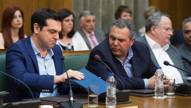 Greek PrIme minister Alexis Tsipras, left, and Greek Defense Minister and party leader of the Independent Greeks Panos Kamenos chat during a cabinet meeting on Thursday, June 2, 2016. Parliament approved a final round of austerity measures Thursday demanded by lenders for the release of further bailout loan installments [Image: AP Photo/Petros Giannakouris/The Associated Press]
