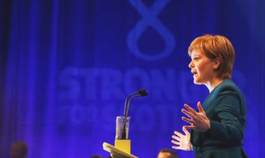 Nicola Sturgeon speaking at the SNP conference [Image: The Guardian].
