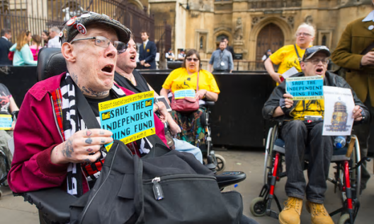 A protest by disability rights campaigners in Westminster in June 2015 [Image: Dominic Lipinski/PA].