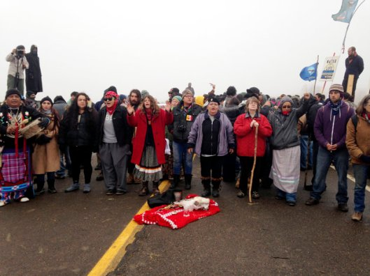 "Protesters fighting construction on the Dakota Access Pipeline block a highway near Cannon Ball, North Dakota, on October 26. Facebook users are ""checking in"" at Standing Rock Indian Reservation in solidarity [Image: James MacPherson/AP]."