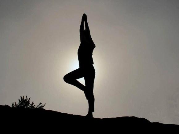 Silhouette d'une femme faisant du yoga à l'extérieur.