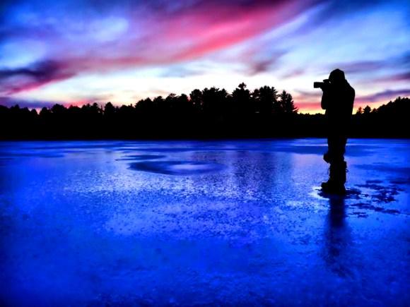 Homme prenant une photo d'un magnifique ciel nocturne coloré.