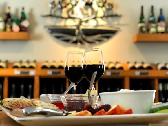Vin et fromage au vignoble Georgian Hills. Le saisissant emblème de métal du vignoble est une œuvre personnalisée de Michael Pocock