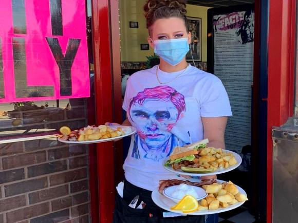 Une femme portant un masque apporte trois assiettes de nourriture sur la terrasse