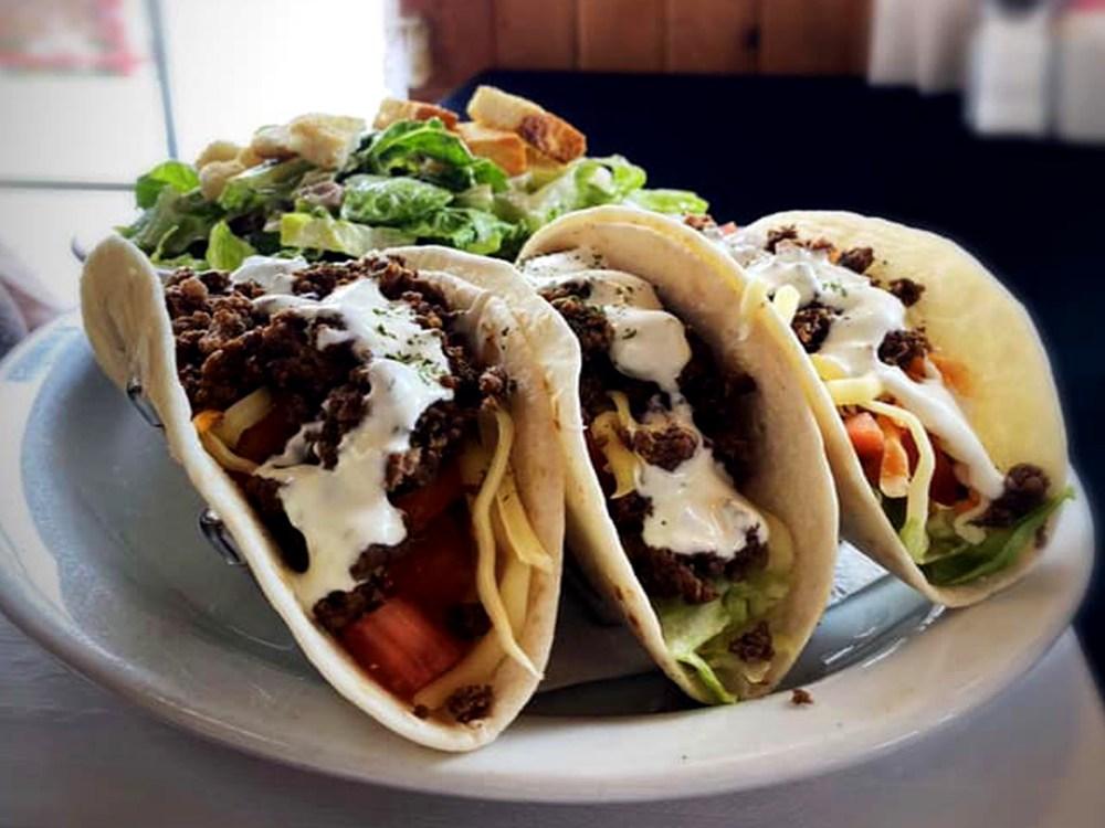 Gros plan de trois tacos et une salade
