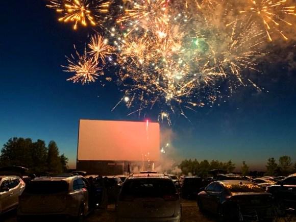 Des feux d'artifice illuminent le ciel au-dessus d'un ciné-parc bondé