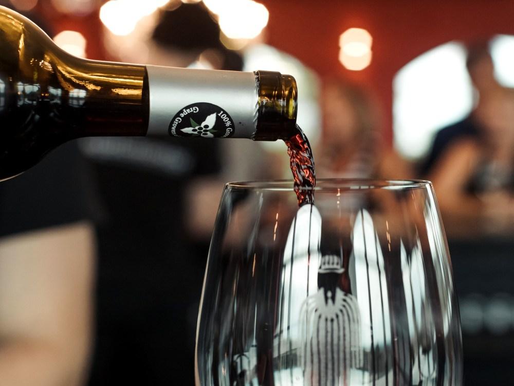 Une personne versant du vin rouge dans un verre