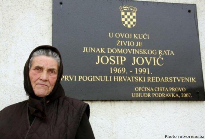 Marija Jovic devant la plaque commémorative en l'honneur de son fils Josip Jovic, 1ère victime de la guerre de Croatie