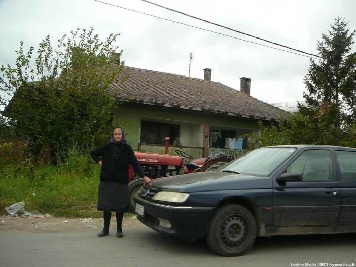Vieille dame près d'une voiture sur la route à la sortie de Umraci en Serbie centrale