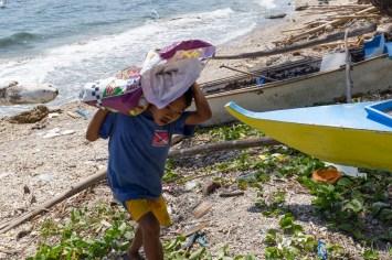 Apo Island - enfant transporte des pierres et coraux