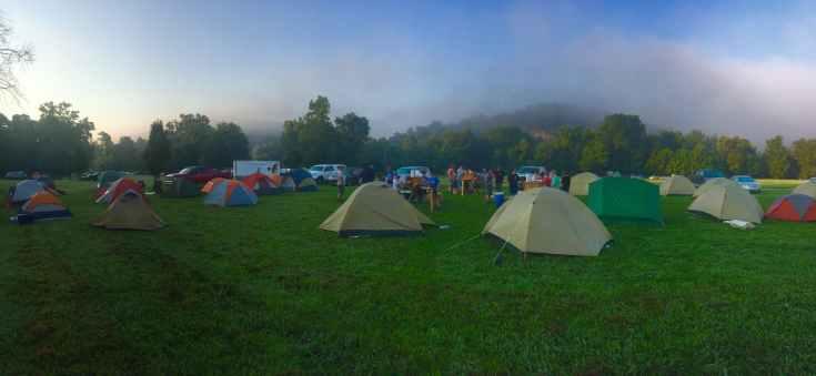 tents on green grass field near mountain
