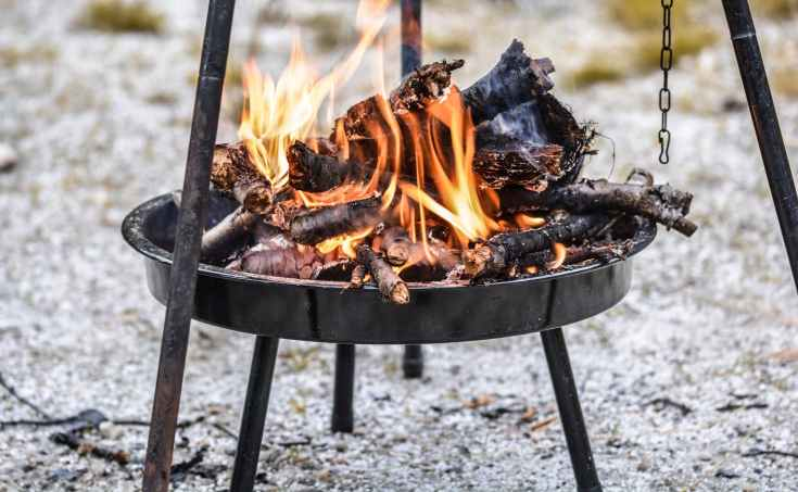 firewood burning in black steel round tray