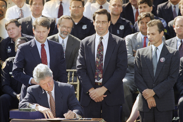 FILE - President Bill Clinton signs the $30 billion crime bill during a ceremony on the South Lawn of the White House in Washington.