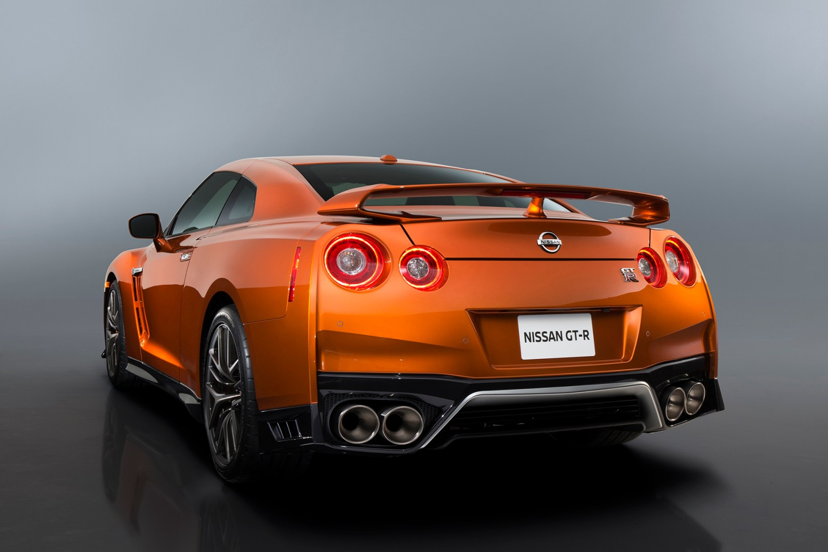 "The 2017 GT-R's exterior receives a thorough makeover. The new ""V-motion"" grille, one of Nissan's latest design signatures, has been slightly enlarged to provide better engine cooling and now features a matte chrome finish and an updated mesh pattern. A new hood, featuring pronounced character lines flowing flawlessly from the grille, has been reinforced to enhance stability during high-speed driving. A freshly designed front spoiler lip and front bumpers with finishers situated immediately below the headlamps give the new GT-R the look of a pure-bred racecar, while generating high levels of front downforce."