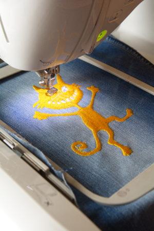 вышивка желтого веселого кота на детских джинсах