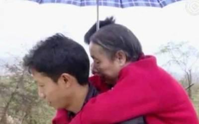 Мъж носи майка си на гръб