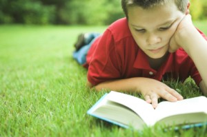 boy-reading-on-grass