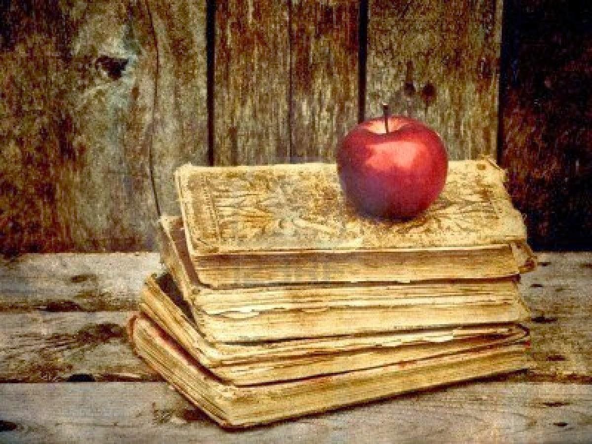 pila-de-libros-antiguos-con-una-manzana-sobre-un-fondo-gru