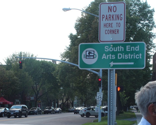 A sign announcing the South End Arts District on Main Street, in Burlington. A sticker covers the information symbol. Photo by Jess Wisloski/VTDigger