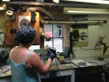 """Terry Zigmund, welding a glass piece she's constructing for her next craft fair. Zigmund says she feels the engagement process run by Burlington City Arts was """"a joke."""" Photo by Jess Wisloski/VTDigger"""
