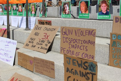Cardboard signs lean on the steps of the Statehouse during the March for Our Lives rally on Saturday, March 24. Taped above them are photos of those who have died in mass shootings. Photo by Kelsey Neubauer/VTDigger