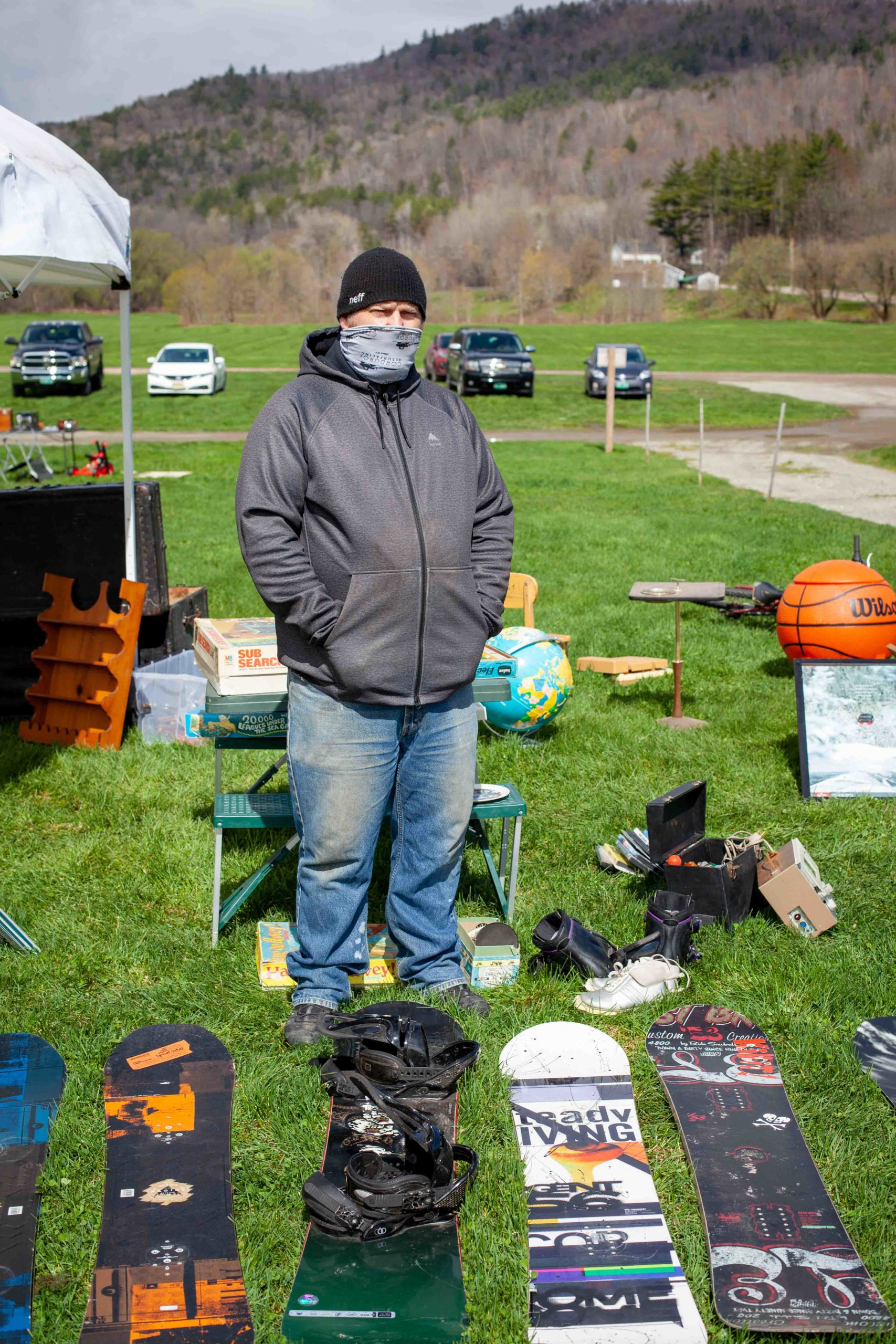 Man in front of row of snowboards on grass with other sale items in background