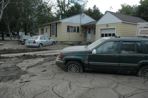 The White River left a sea of mud behind, coating these cars along Route 14 in West Hartford. VTD/Andrew Nemethy