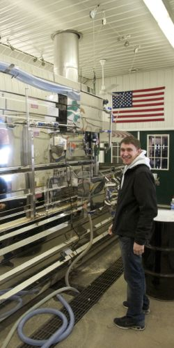 Evan Branon, one of Tom and Cecile's four sons, stands near the Branon Family Maple Orchards evaporator.