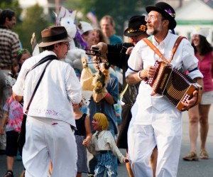 The Midnight Capers Morris dance troop leads a procession of children along Main Street during the New World Festival in Randolph last September. (Photo by Bob Eddy, courtesy of the Herald of Randolph)