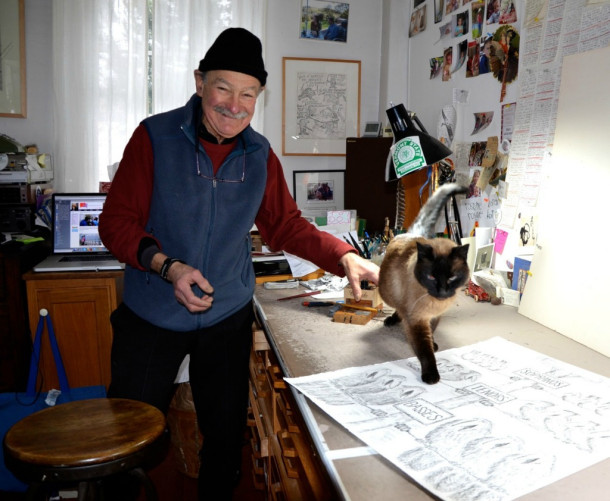 """Ed Koren's vocal Siamese feline, """"Catmandu,"""" prowls on one of the illustration tables Koren uses to draw in his Brookfield studio. Photo by Andrew Nemethy"""