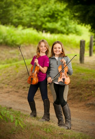 Two young musicians pose with their fiddles in a field during a break from practice at a fiddling camp in South Royalton. Copyright photo by Jack Rowell