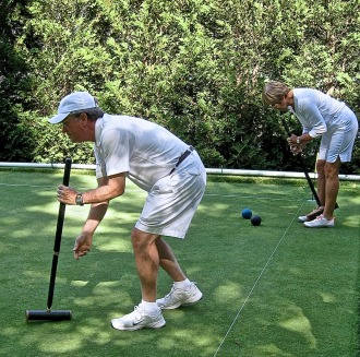 More than one game can be played at one time on a croquet course, but these two competitors are just warming up the day before the competition begins. The white string on the ground is a line marking the boundary of the course. Photo by Nancy Price Graff