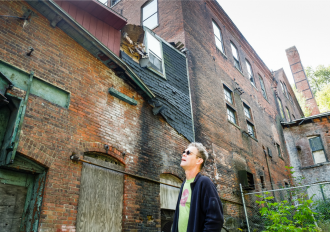 Painter Charlie Hunter examines the ruins of the massive Moore and Thompson Paper Mill Complex in Bellows Falls, which has been shuttered for nearly a century. Photo by Mark Bushnell