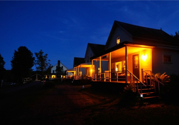 Cabins at Quimby Country glow at night. The main lodge is visible In the background. Photo by Mark Bushnell