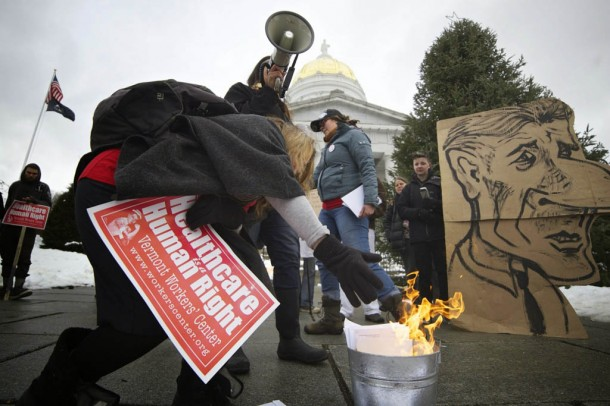 A protester burns a medical bill in a demonstration against Gov. Peter Shumlin's decision not to pursue single payer health care in the next legislative session. Photo by John Herrick/VTDigger