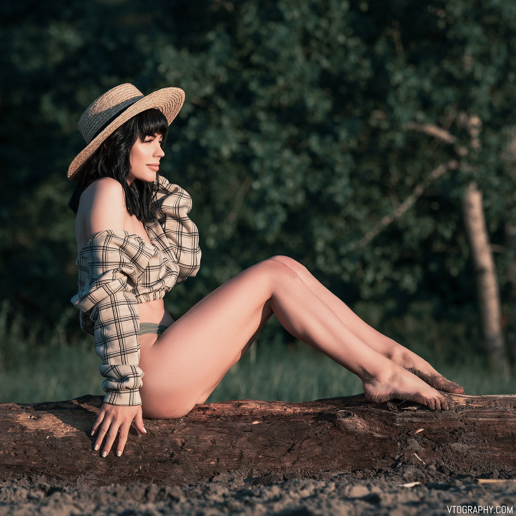 Sitting on a log, wearing a hat