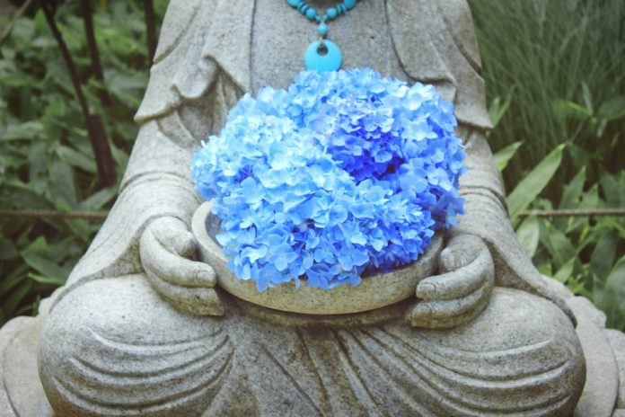 statue holds a bowl filled with striking blue beautiful flowers