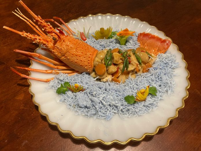 Coconut lobster with scallops and vegetables on a bed of rice.